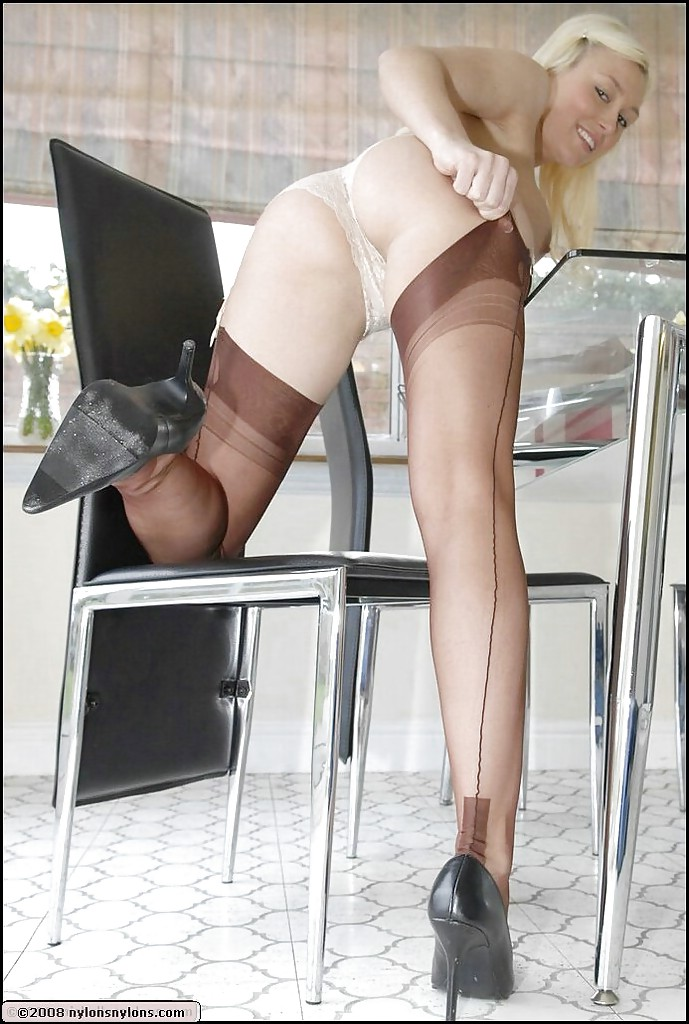 Busty babe in nylon stockings stripping and posing on high heels