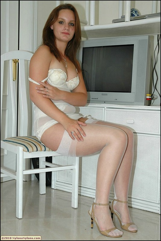 Adorable cutie in white lacy lingerie and nylon stockings demonstrating her legs