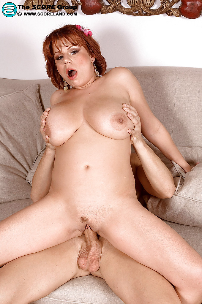 Busty redhead fucks her shaved snatch