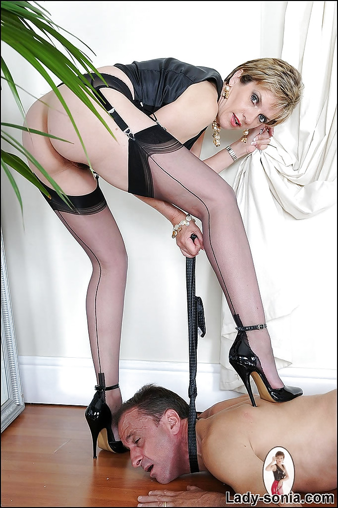 ... Busty mature femdom on high heels tortures her naked manslave ...
