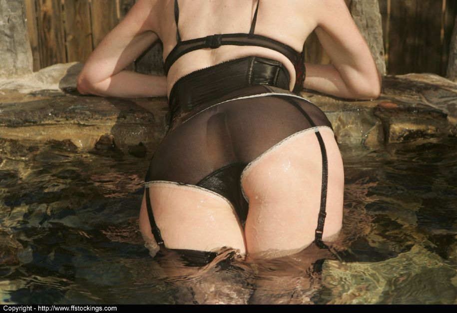 Tempting mature lady in black nylon stockings posing in the pool