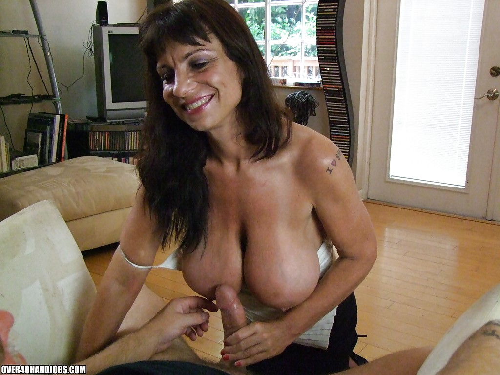 ... Fuckable mature brunette with massive knockers gives a sensual handjob  ...