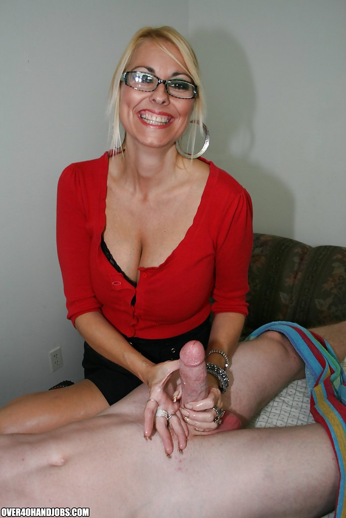 ... Fully clothed mature blonde with big tits gives a sensual handjob ...