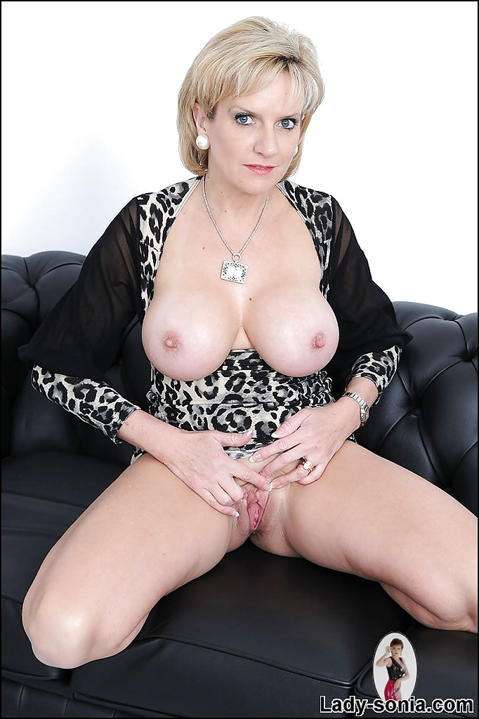 Naughty mature lady uncovering her round boobs and fingering her cunt