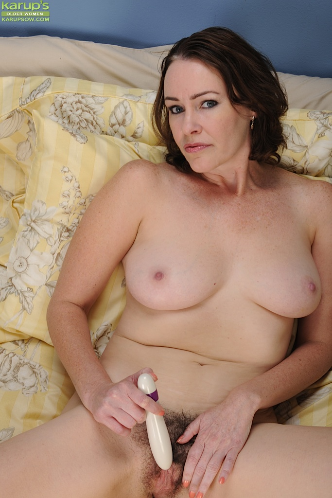 Bosomy MILF taking off her sheer lingerie and toying her hairy cunt