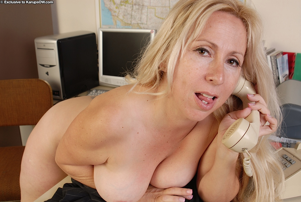 ... Lusty mature blonde with big tits posing nude and acting sassy in her  office ...