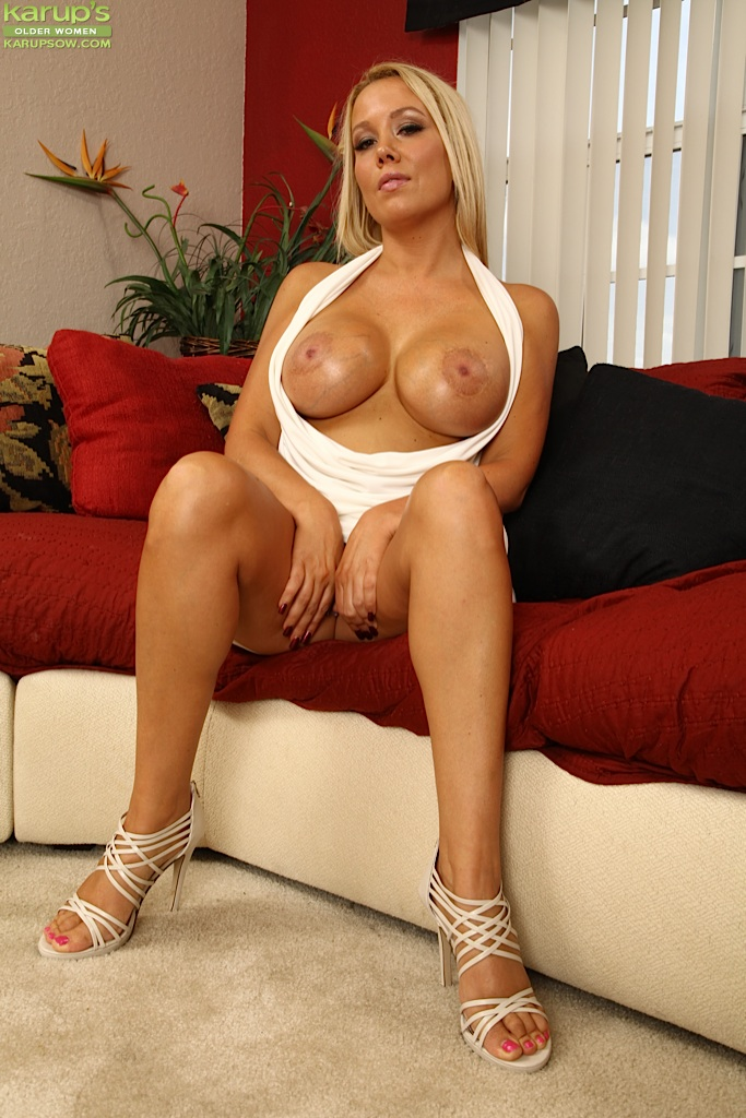 Mature blonde masturbates on sofa