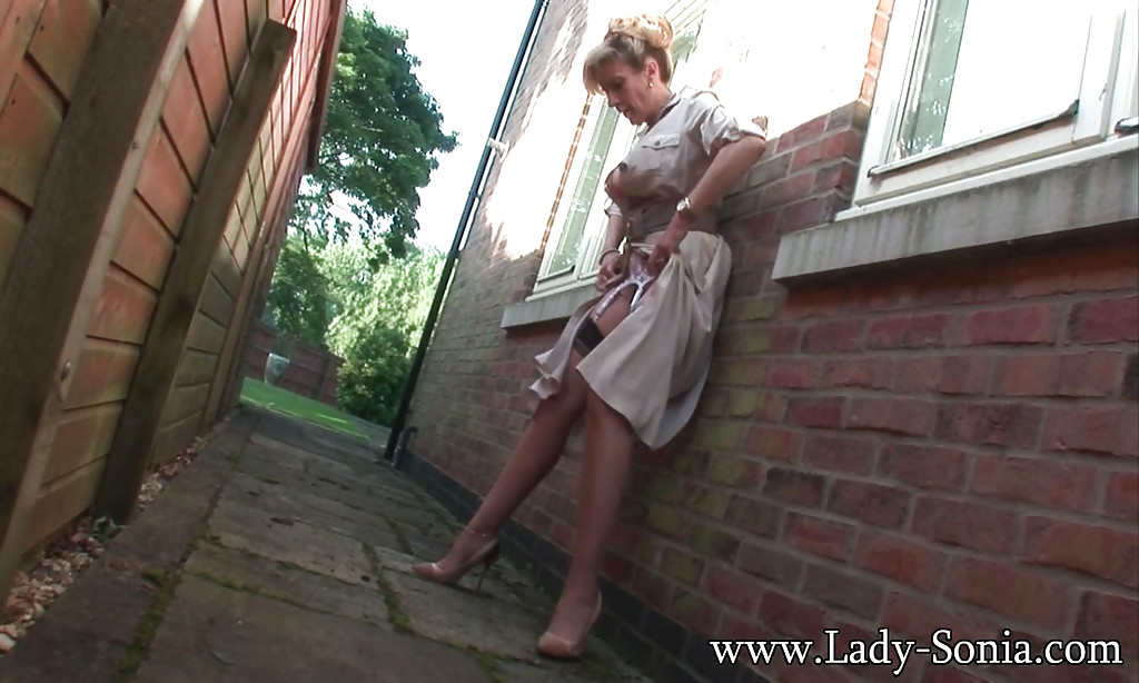 ... Big tits mature slut Lady Sonia is pissing somewhere behind a house ...