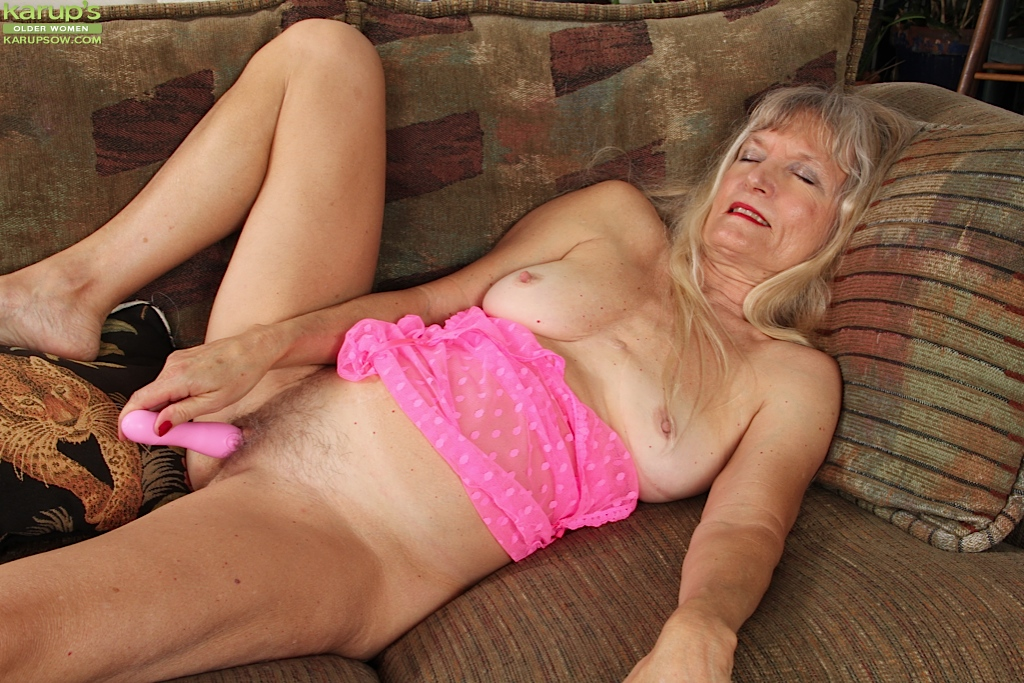 Mature blonde on bed masturbates her pussy