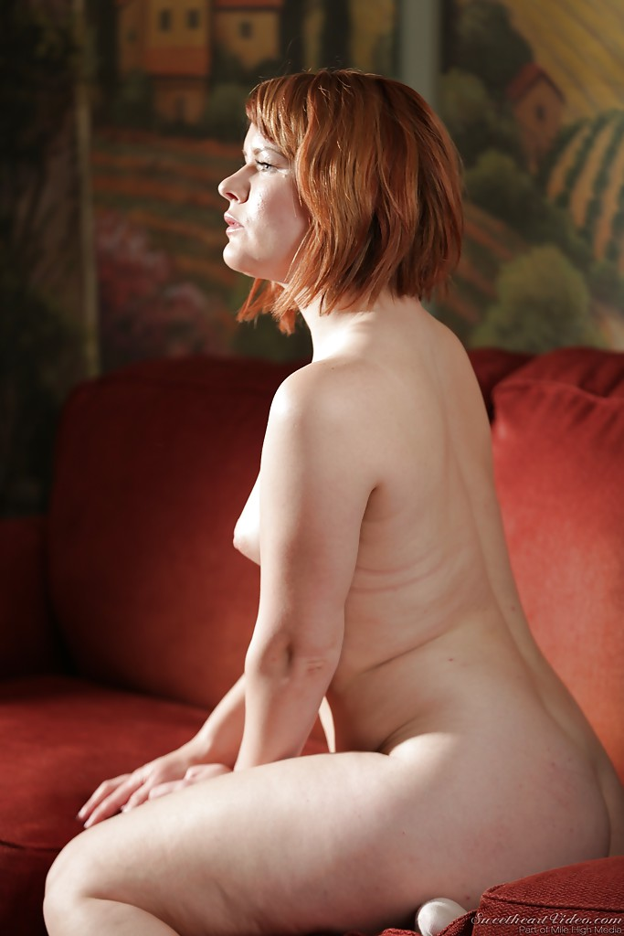 busty posing redhead on couch
