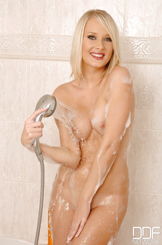 Blonde babe Deni M showing off swollen clitoris in the shower