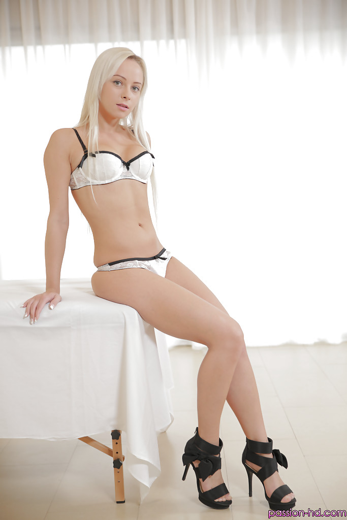 Stunning blonde beauty Naomi Nevena crossing bare legs after stripping naked