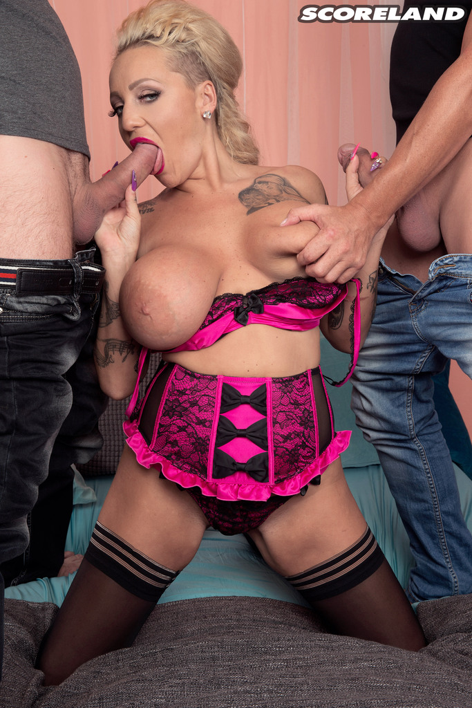 Weird European MILF with huge fake tits and a tattooed body sucks two cocks