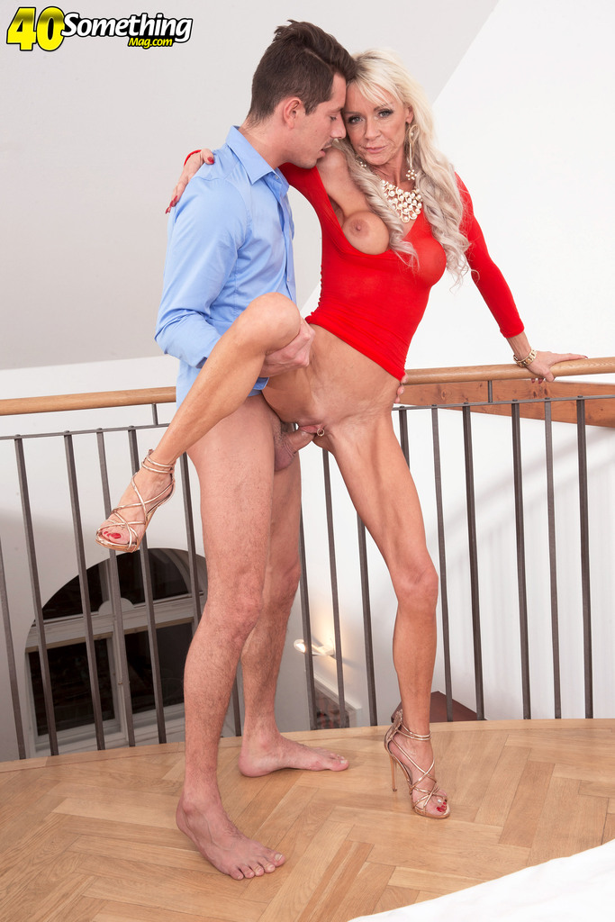 Older blonde lady Alexis Starr seduces a younger man in a tight red dress