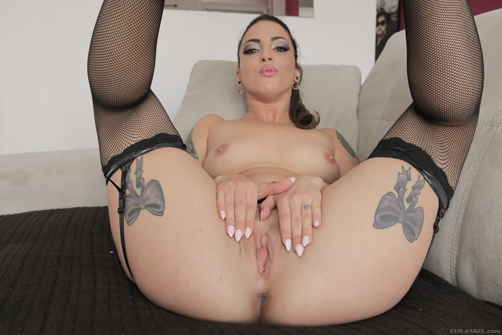 Tattooed solo girl Medusa shows off her pussy in garters and nylons