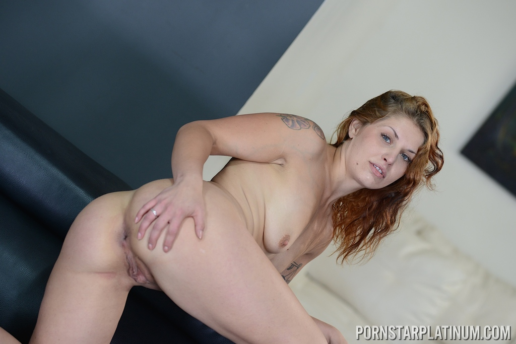 Redhead model Fallon West slips off skirt and panties to model naked