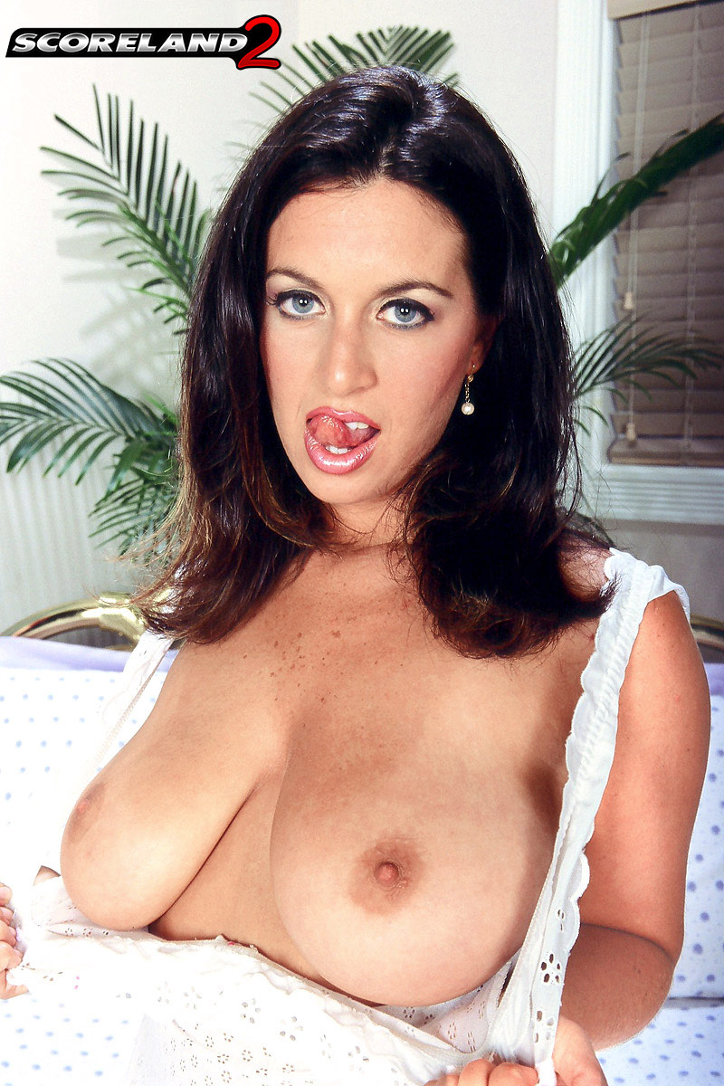 Solo model Angie Sweet unleashes her natural tits as she disrobes on bed