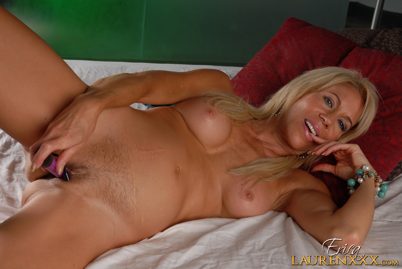 Older blonde Erica Lauren toys her pussy and asshole at the same time on a bed