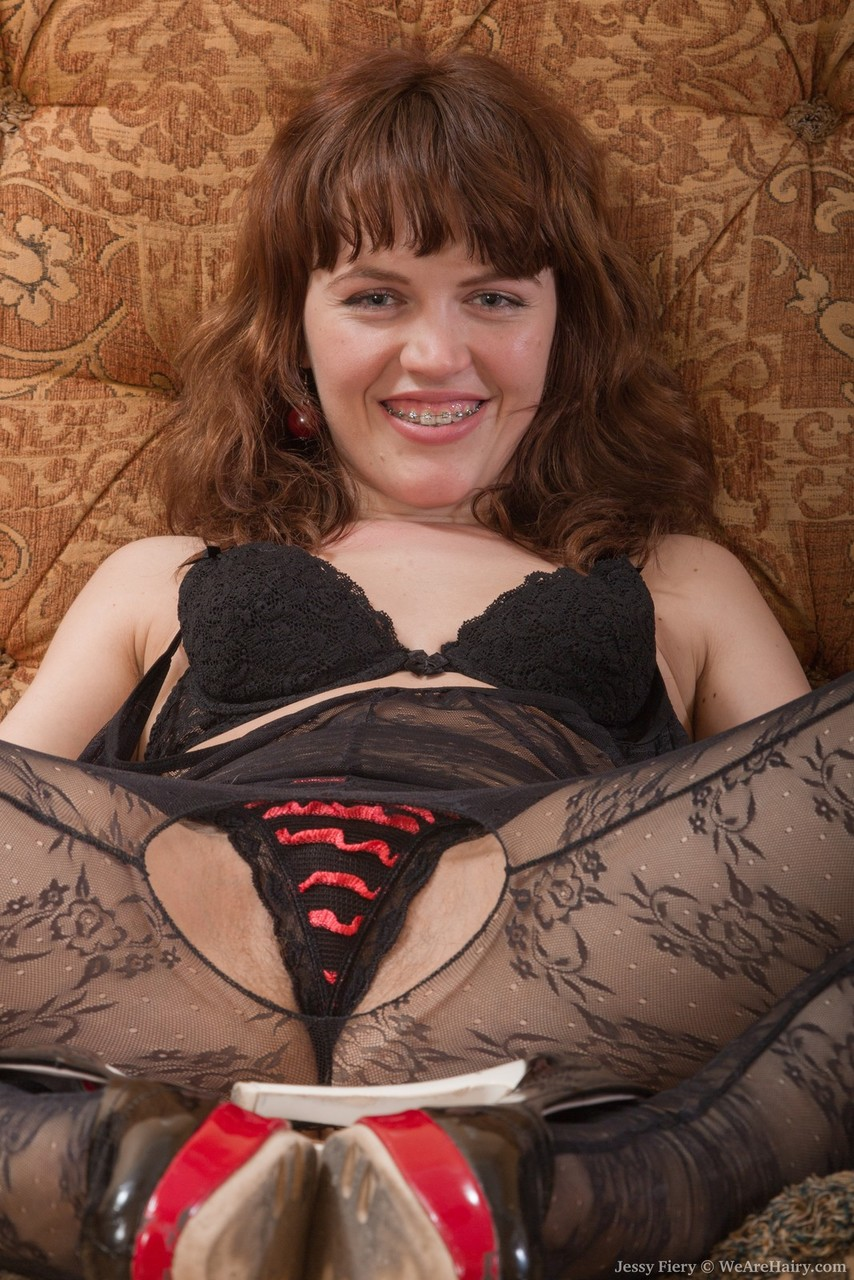 Amateur girl Jessy Fiery spreads her hairy pussy after removing a bodystocking