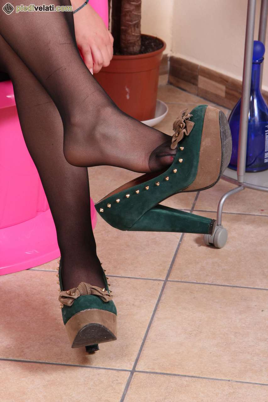 Non nude brunette frees her nylon clad feet from suede pumps