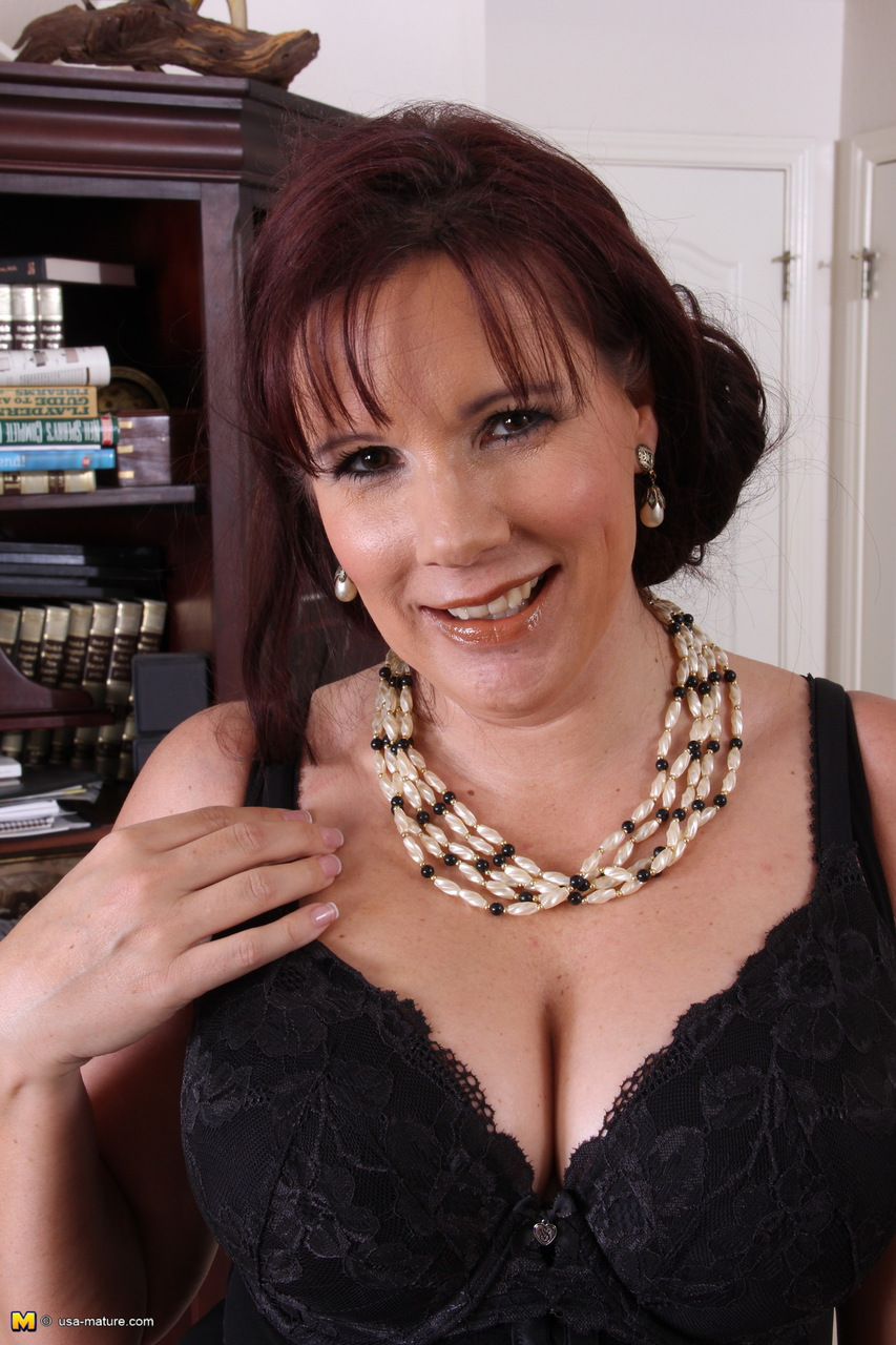 thick aged woman takes off her dress and black lingerie to pose