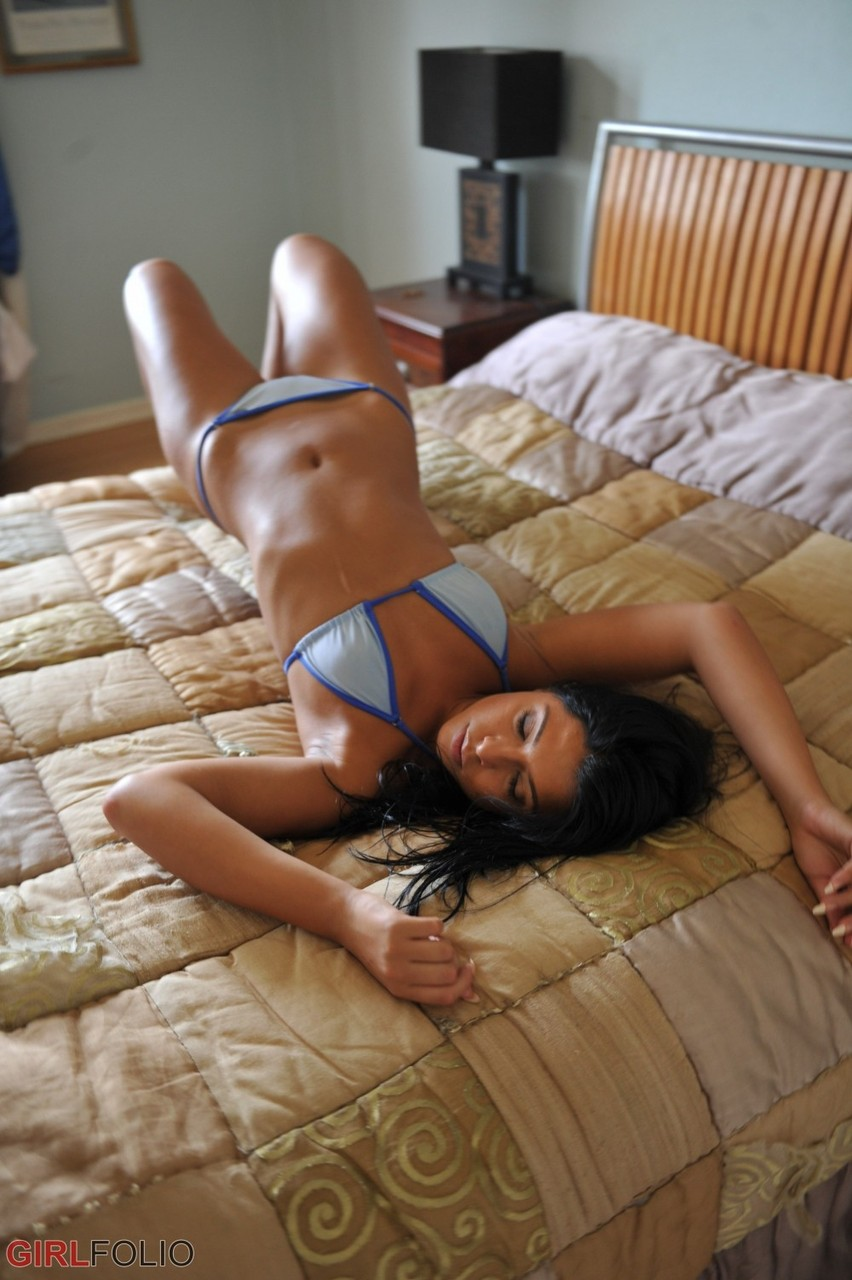Young solo girl Cara De la Hoyde takes off her skimpy bikini on her daybed