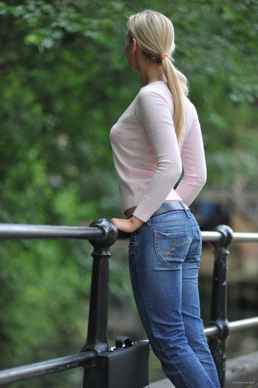 Blonde model in blue jeans and heels heads indoors to pose in the nude
