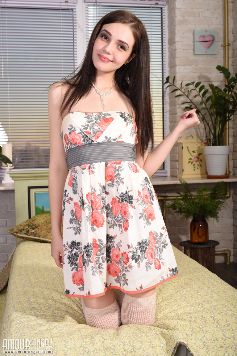 Pretty young Lily doffs her dress to pose nude on her knees in white stockings