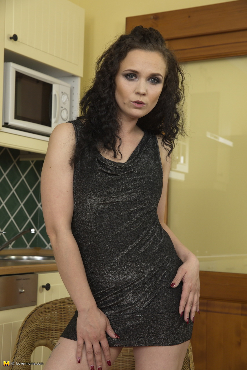 Brunette mom exposes her small tits and bald slit in her kitchen