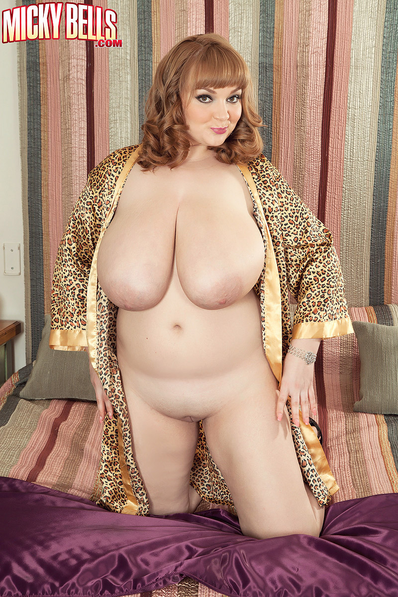 Thick redhead Micky Bells displays her giant boobs while getting changed