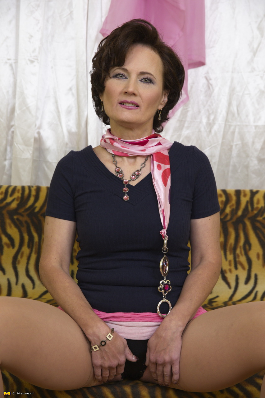 Older dame in pink skirt flashes upskirt panties and some stocking tops