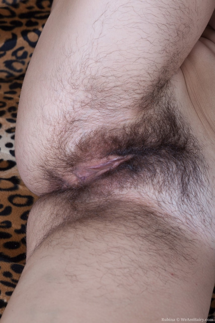 Glasses clad amateur Rubina bends over naked for closeup of very hairy beaver
