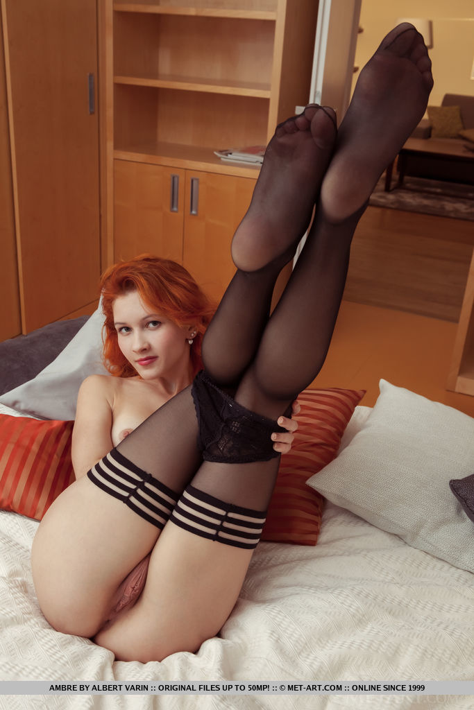Pale redhead shows off her delectable pussy in sexy stockings on her bed