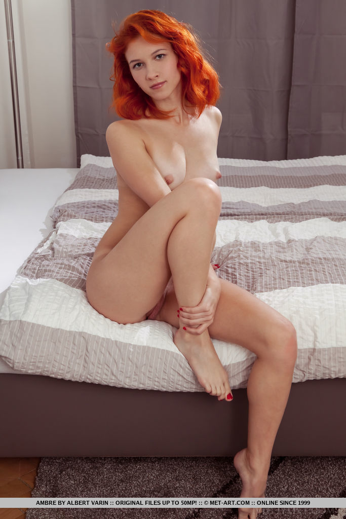 Young redhead Ambre gets naked in bedroom before showing her meaty pussy lips