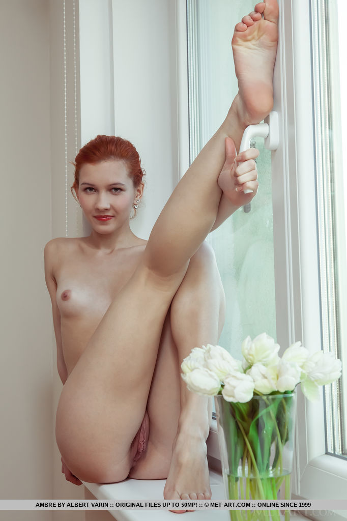 Pale redhead Ambre spreads her long legs to display her moist and puffy pussy