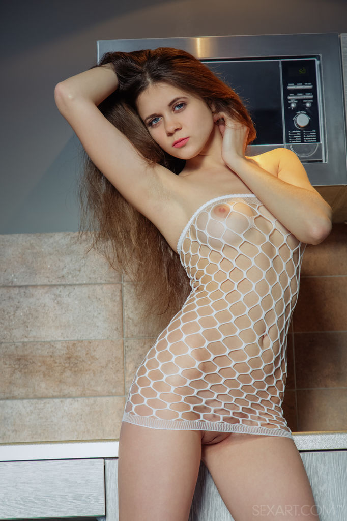 Teen girl Etna parts her pink pussy in kitchen wearing a fishnet dress