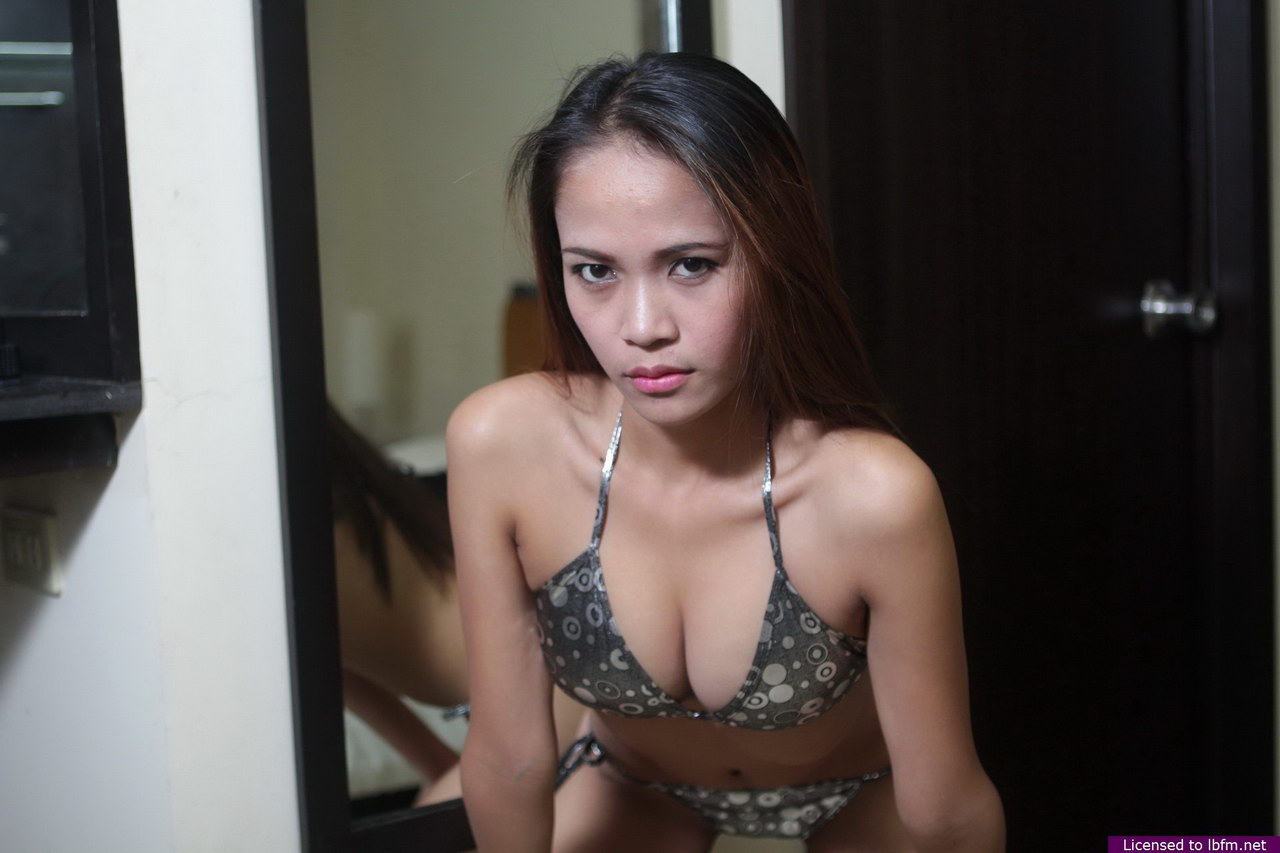 Young Asian girl showcases her bald pussy up against a mirror