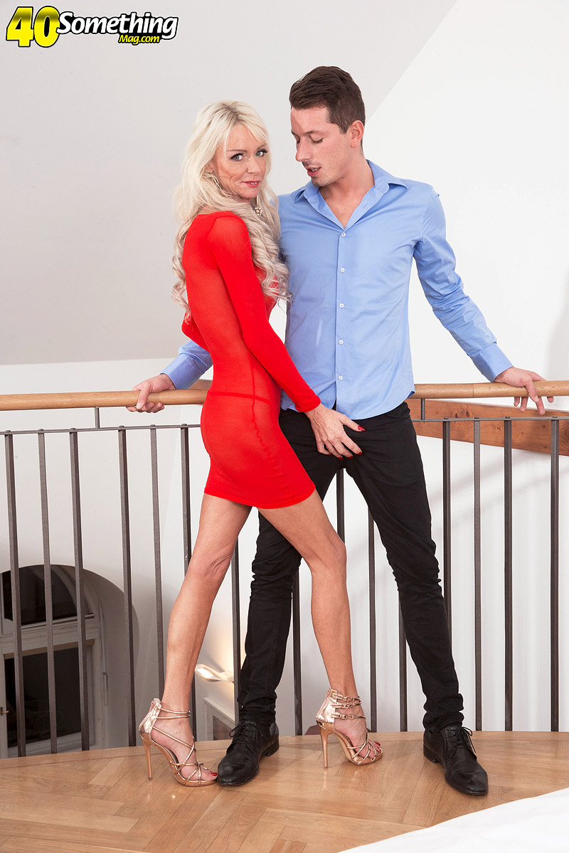 Middle-aged blonde Alexis Starr seduces a younger guy in a red dress