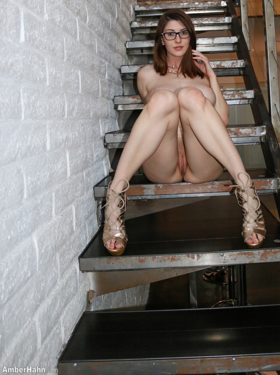 Glasses wearing solo girl Amber Hahn flashes no panty upskirts on staircase