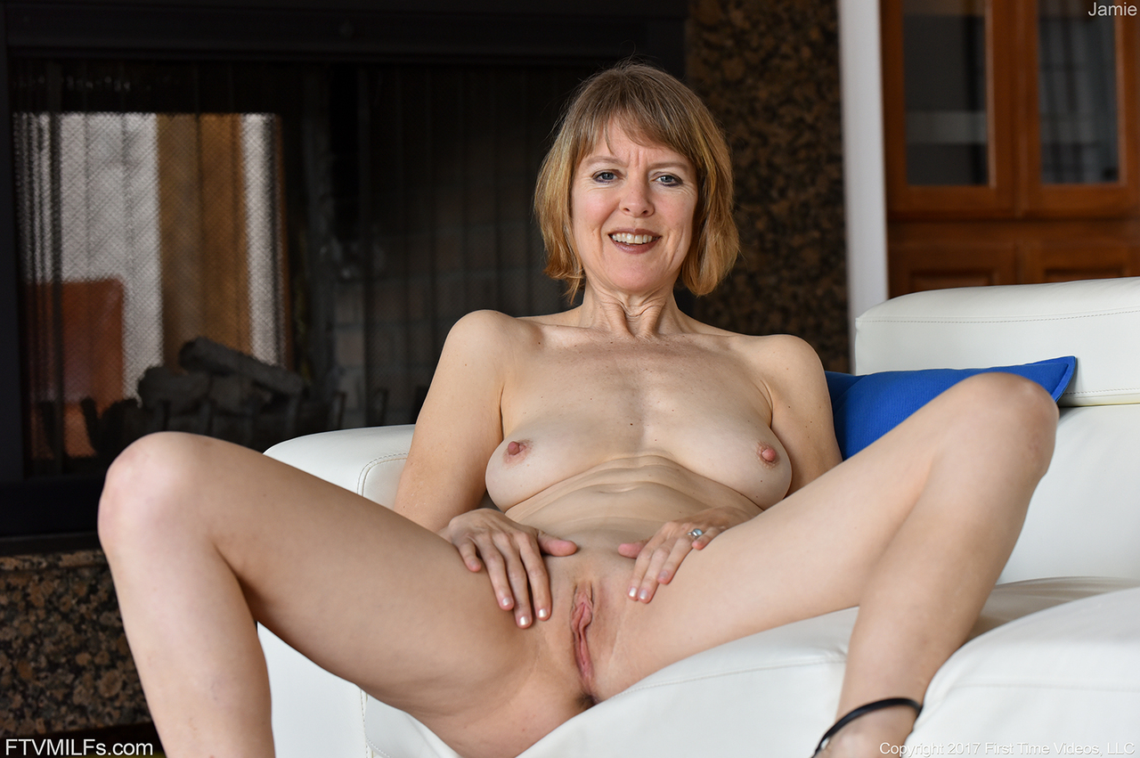 older lady with short hair flaunts her small tits and shaved pussy