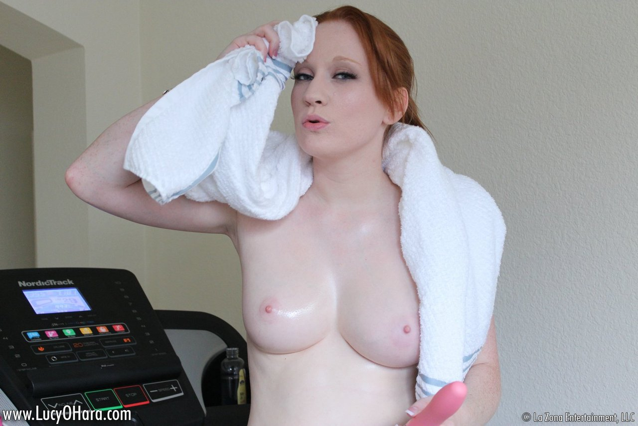 Fit redhead Lucy OHara pauses her workout to shove a dildo in her tight pussy