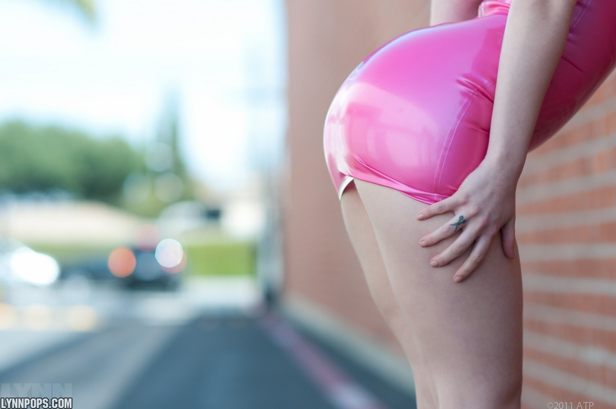 Amateur model Lynn Pops struts in parking lot wearing a pink latex dress