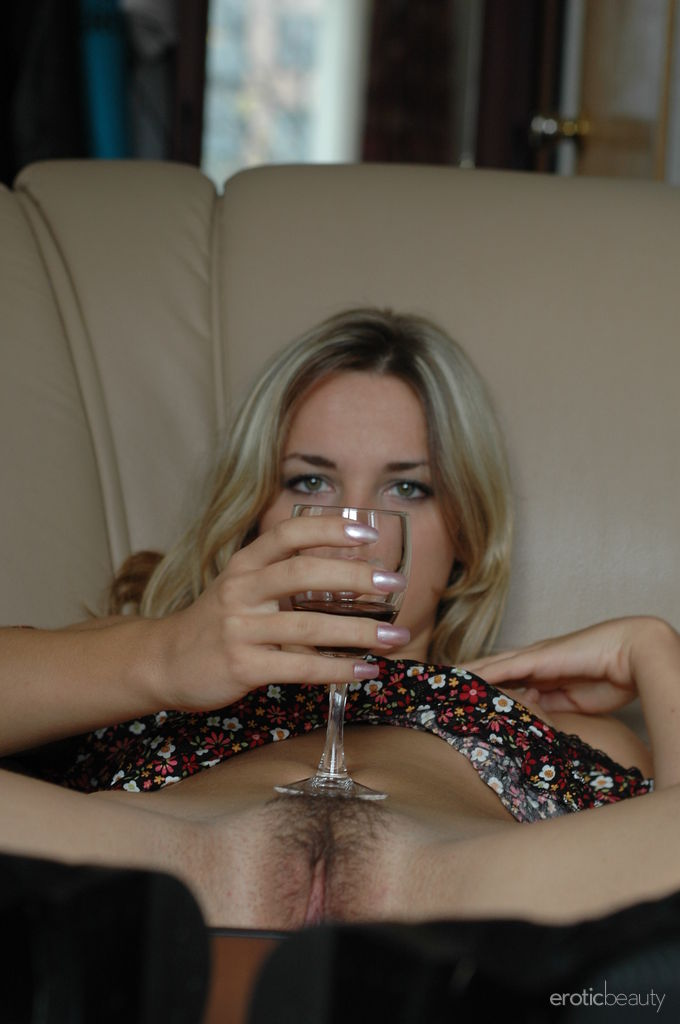 Pretty Natalia B enjoys a glass of wine while she shows off her hairy beaver
