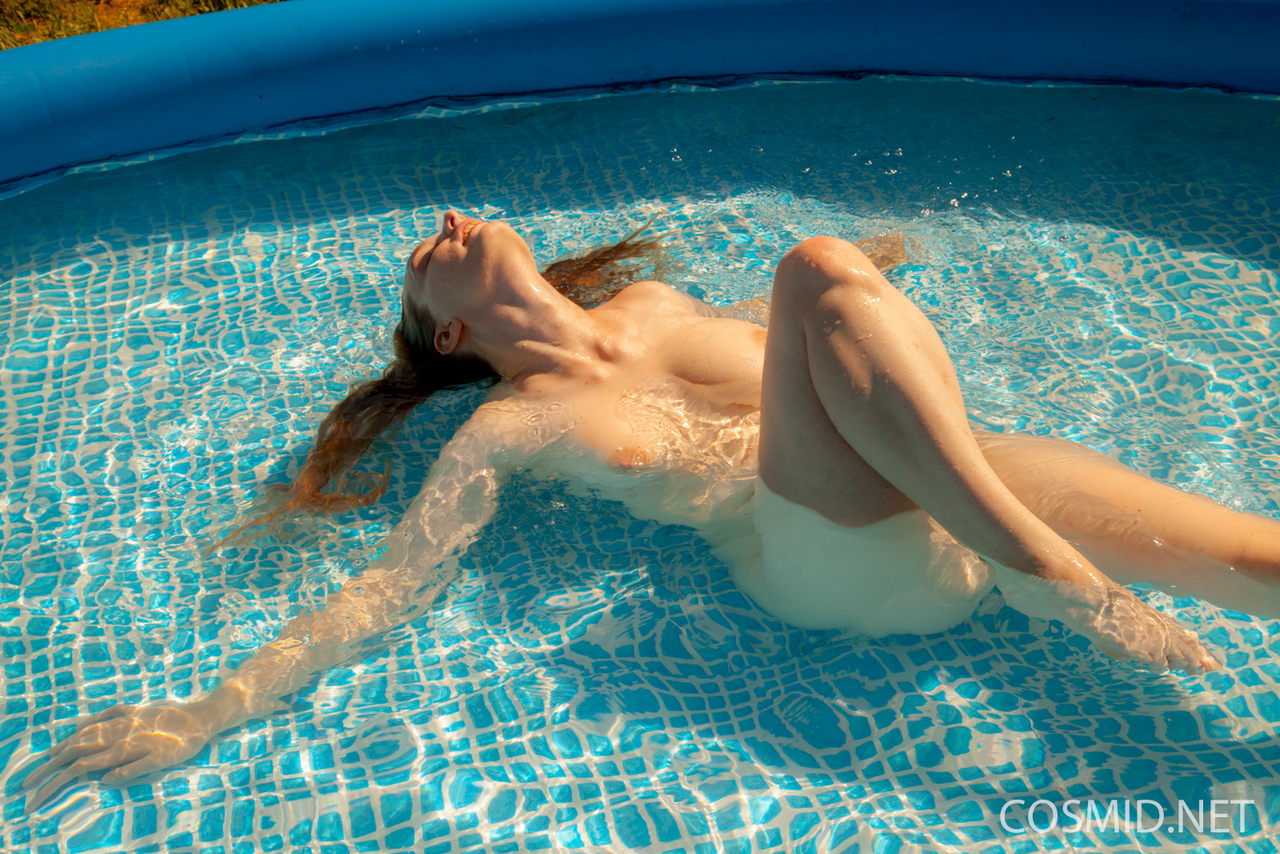 Natural redhead Julia Fleming frees her big natural tits in above ground pool