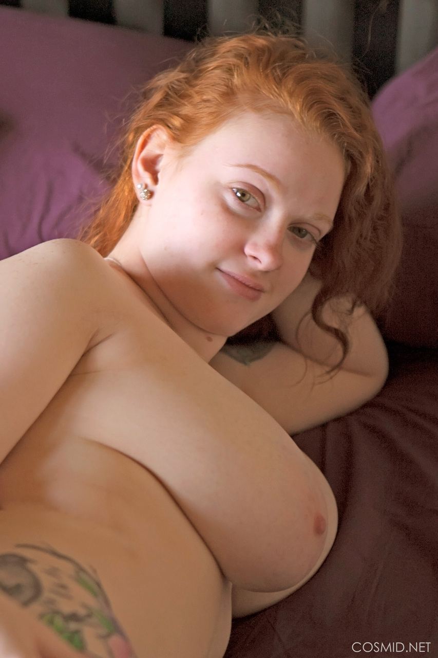 Tattooed redhead with huge floppy tits romping naked on the bed