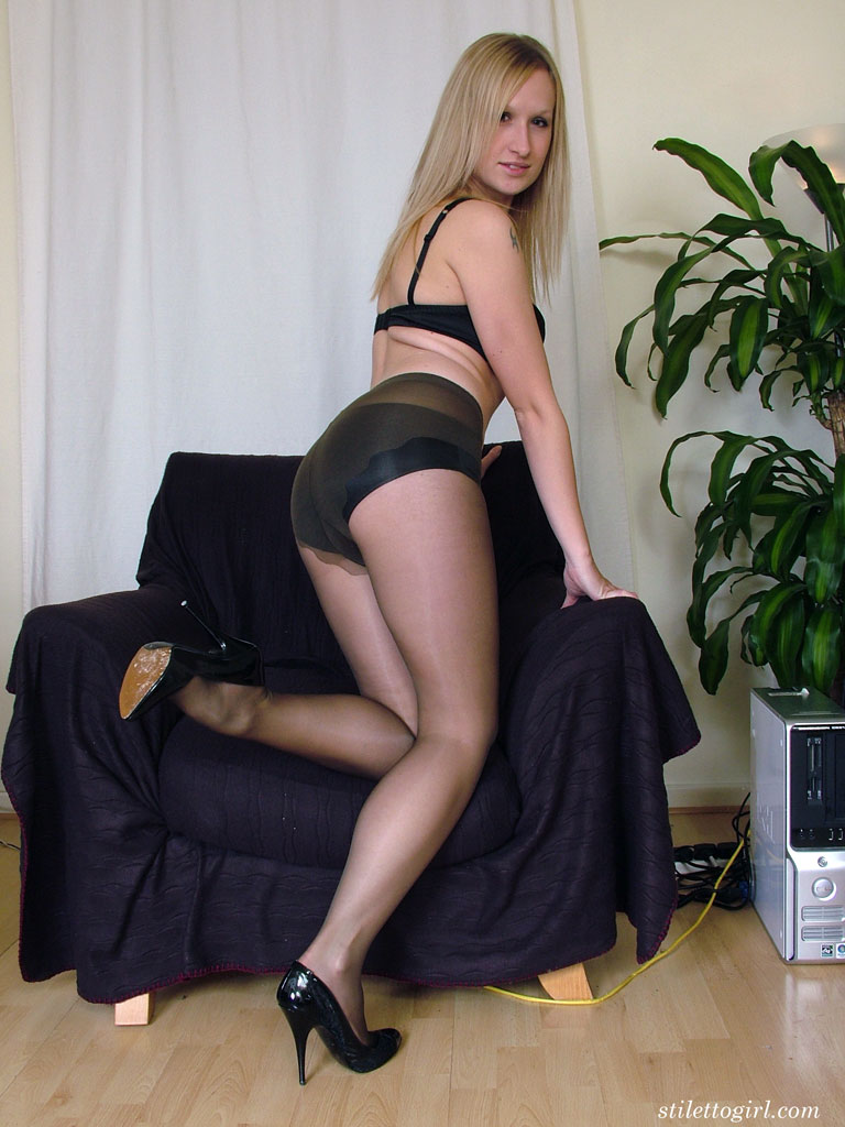 Blonde female displays her shapely legs in black pantyhose and pumps