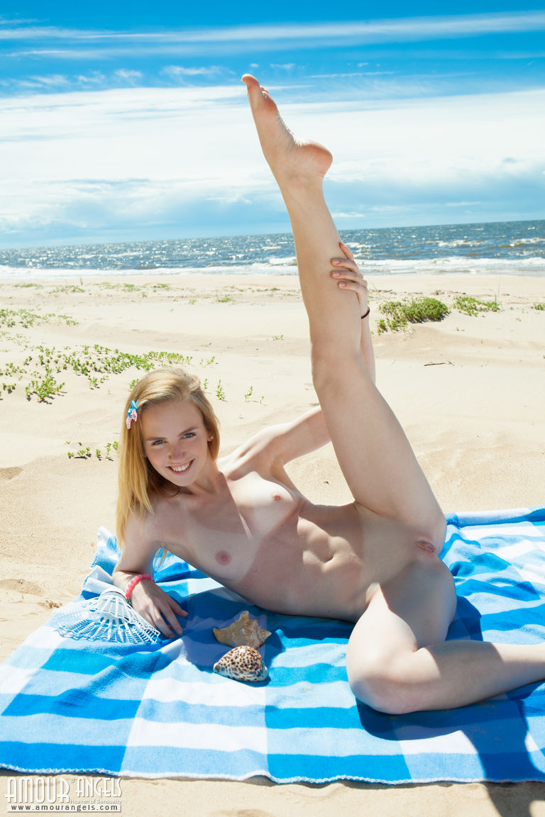 Blonde doll Belonika sheds her swimsuit to spread nude in the beach sand