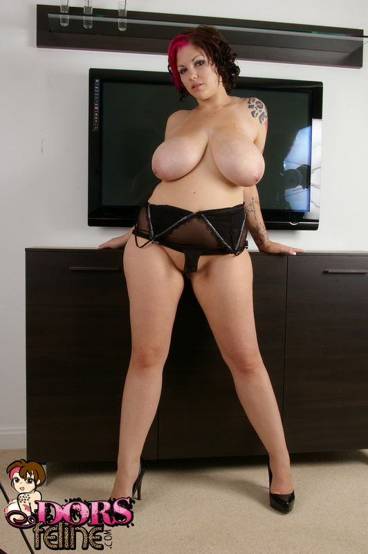 Tattooed BBW Dors Feline unleashes her huge tits as she removes sheer lingerie