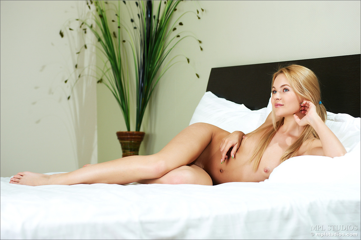 Beautiful girl with blonde hair models totally naked in solo action