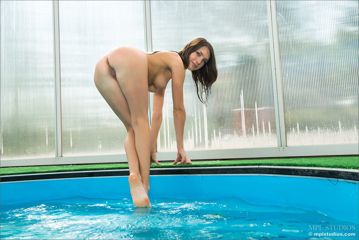 Beautiful girl removes her dress before going skinny dipping in covered pool